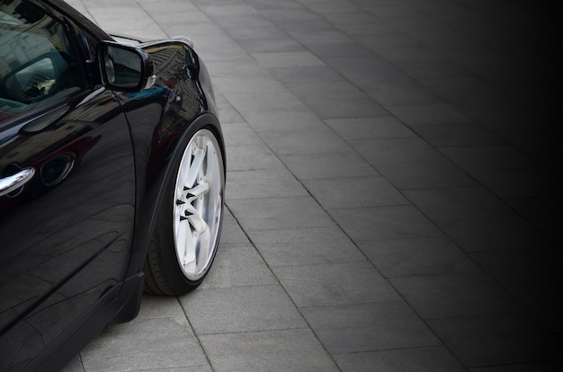 Diagonal view of a black glossy car with white wheels, which stands on a square of gray tiles Premium Photo