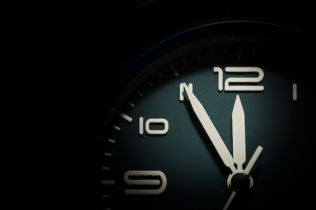 Dial of a clock showing five minutes to twelve Premium Photo