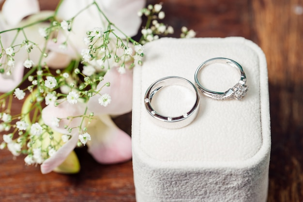 The diamond couple wedding rings is placed on glass. there are nature plant is decoration. Premium Photo