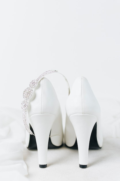 Diamond crown over the pair of white wedding high heels against white backdrop Free Photo