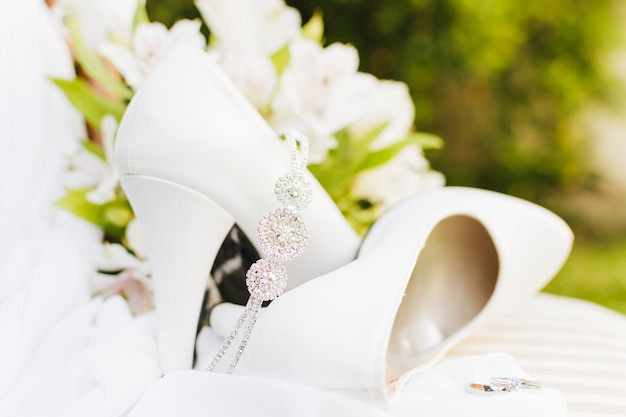 Diamond crown over the pair of white wedding high heels with rings on table Free Photo