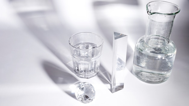 Diamond; glass of water; prism and beaker with shadow on white backdrop Free Photo