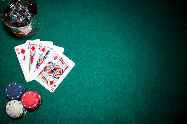 Diamond royal flush playing card; casino chips and whisky glass with ice cubes on green background Free Photo