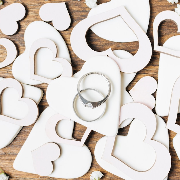 Diamond wedding rings on white heart shapes cut out Free Photo