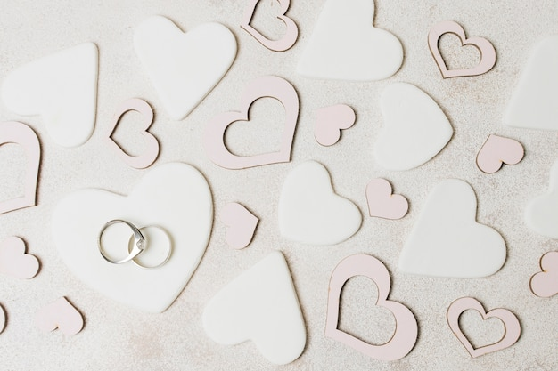 Diamond wedding rings on white and pink heart shape over the concrete backdrop Free Photo