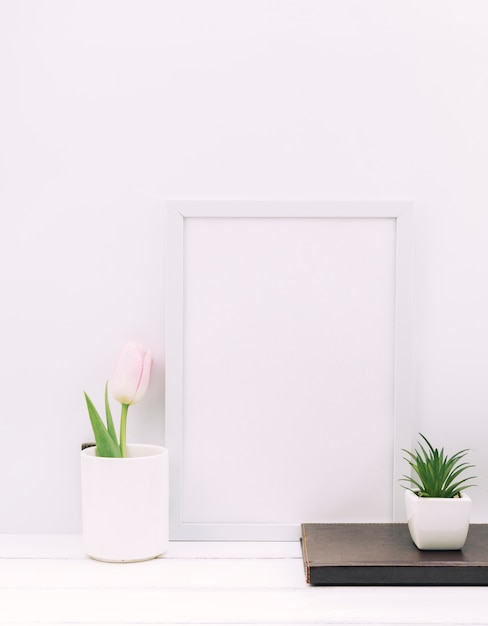 Diary; plant; tulip flower with blank photo frame on white table Free Photo