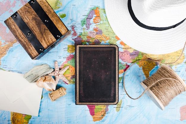 Diario, conchiglia, cappello, scatola di legno e rocchetto, sulla mappa del mondo Foto Gratuite