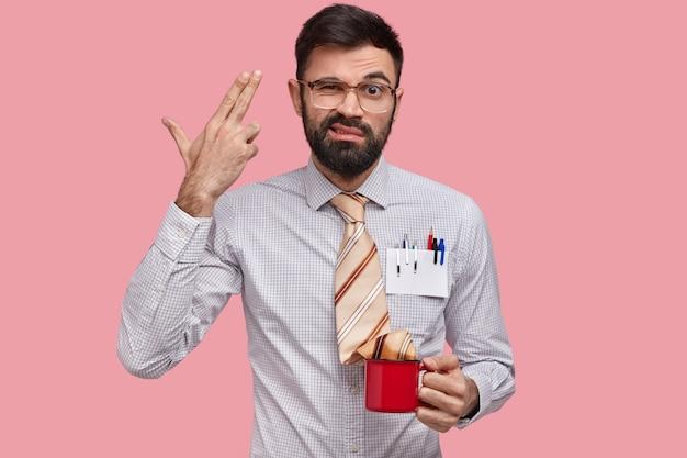 Diasappunto con la barba lunga e prospero esperto di marketing si spara alla tempia, si sente frustrato, ha molto lavoro, indossa una camicia elegante, penne in tasca Foto Gratuite