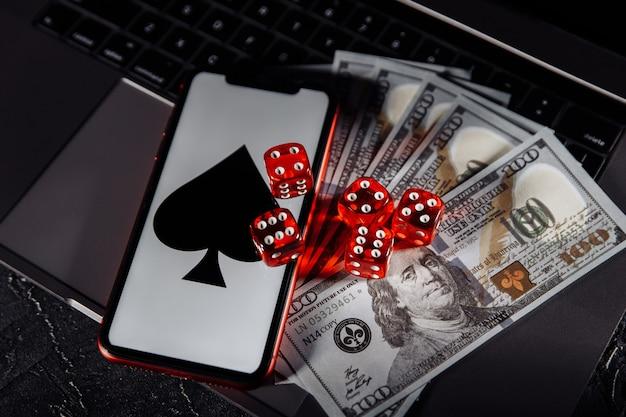 キーボードのサイコロ、スマートフォン、ドル紙幣。オンラインギャンブルの概念 Premium写真