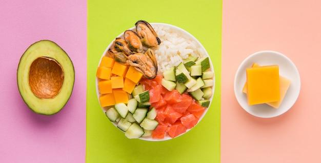 Салат из кубиков тыквы рядом с авокадо и сыром на зеленом, желто-фиолетовом фоне Premium Фотографии