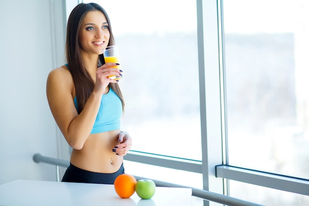 Diet. close-up on fitness young woman drinking orange smoothie in kitchen Premium Photo