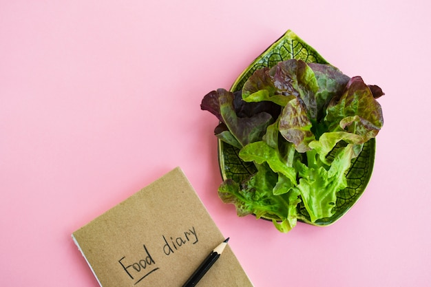 Diet concept. food diary and plate with lettuce on pink Premium Photo