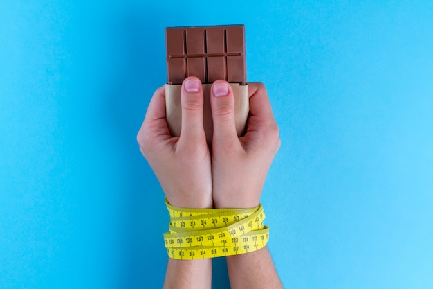 Diet concept, losing weight, chocolate in the hands tied with yellow measuring tape Premium Photo
