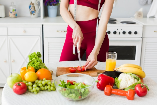 Diet concept with sporty woman in kitchen Free Photo