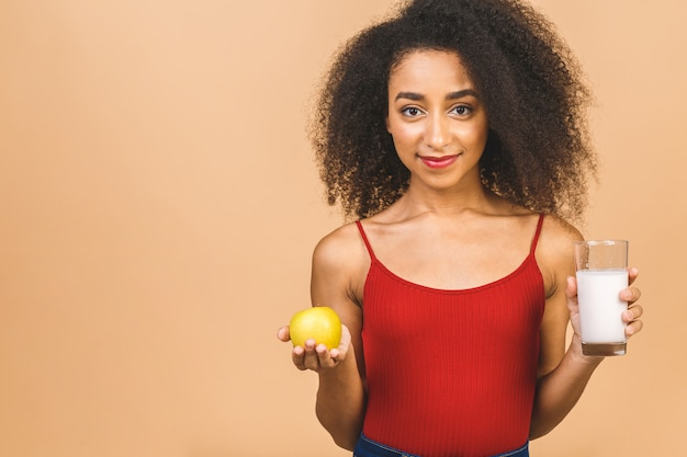 Diet concept. young beautiful woman eating yogurt and green apple as healthy breakfast or snack. Premium Photo