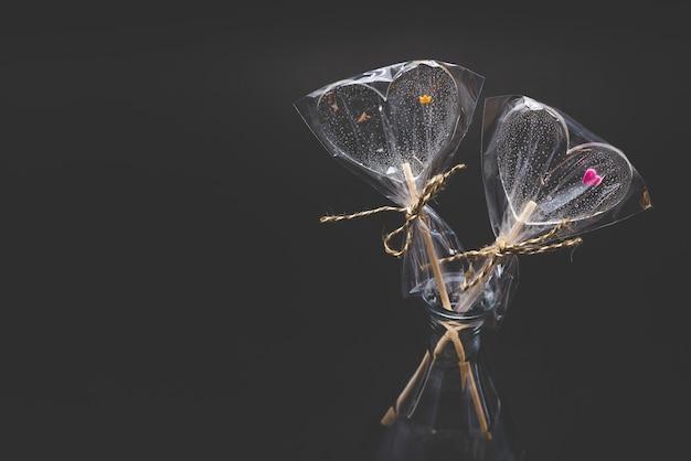 Диета фигурных леденцов. прозрачный и с яркими элементами. на палке. на черном фоне. Premium Фотографии