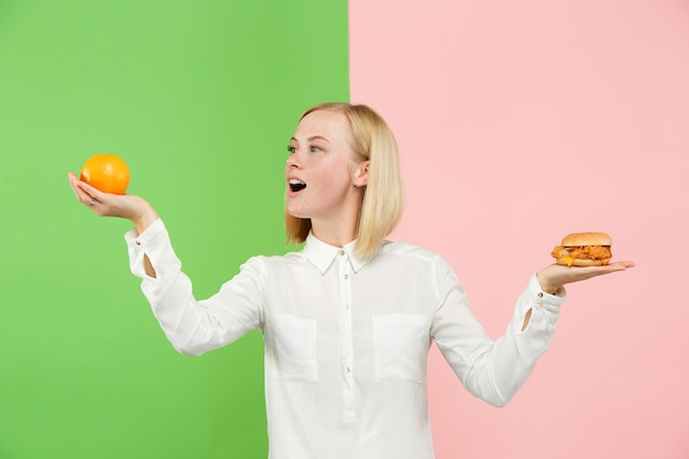 Diet. dieting concept. healthy food. beautiful young woman choosing between fruits and unhelathy fast food Free Photo