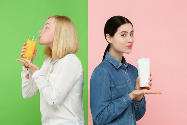 Рацион питания. концепция диеты. здоровая пища. красивые молодые женщины выбирают между фруктовым апельсиновым соком и безвкусным сладким газированным напитком Бесплатные Фотографии