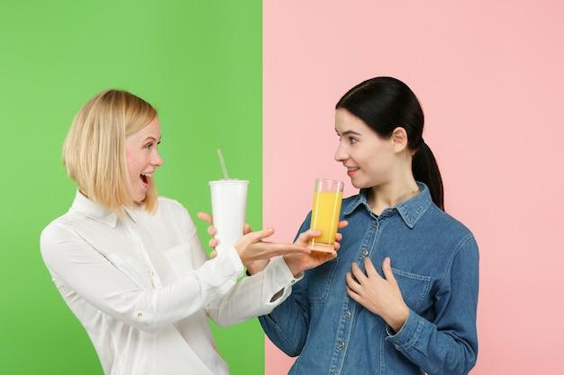 Диета. концепция диеты. здоровая пища. красивые молодые женщины выбирают между фруктовым апельсиновым соком и безвкусным сладким газированным напитком Бесплатные Фотографии
