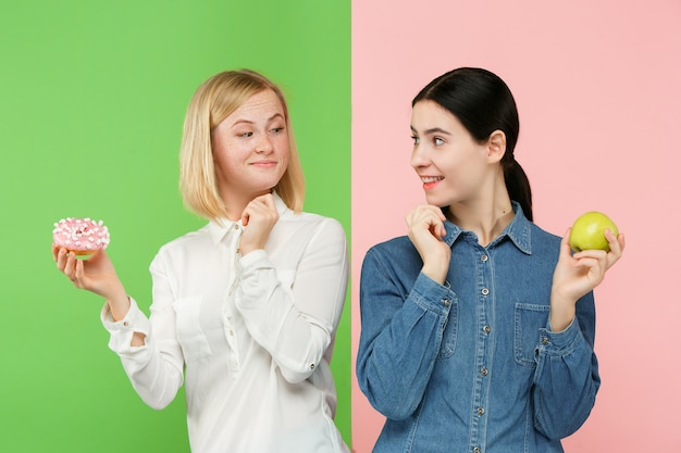 Diet. dieting concept. healthy food. beautiful young women choosing between fruits and unhelathy cake Free Photo