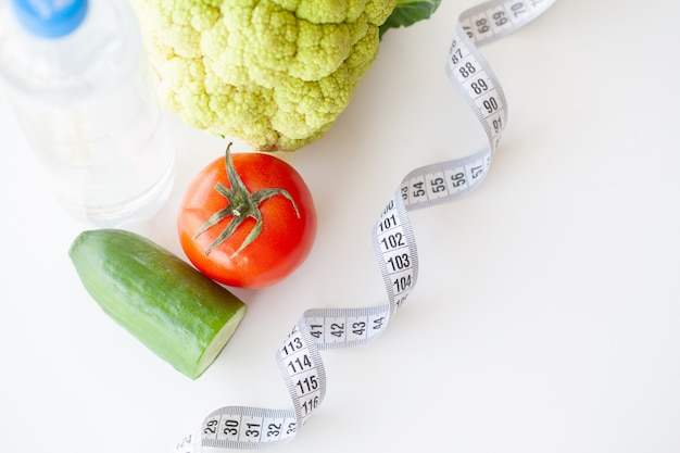 Diet. fitness and healthy food diet concept. balanced diet with vegetables. fresh green vegetables, measuring tape Premium Photo