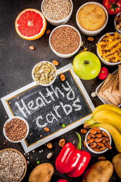 Diet food background concept, healthy carbohydrates (carbs) products -  fruits, vegetables, cereals, nuts, beans, dark blue concrete background top  view copy space | Premium Photo