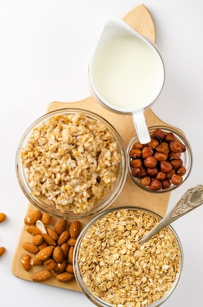Диетическое меню на завтрак с миской овса с орехами и молочной банкой на деревянной доске Premium Фотографии