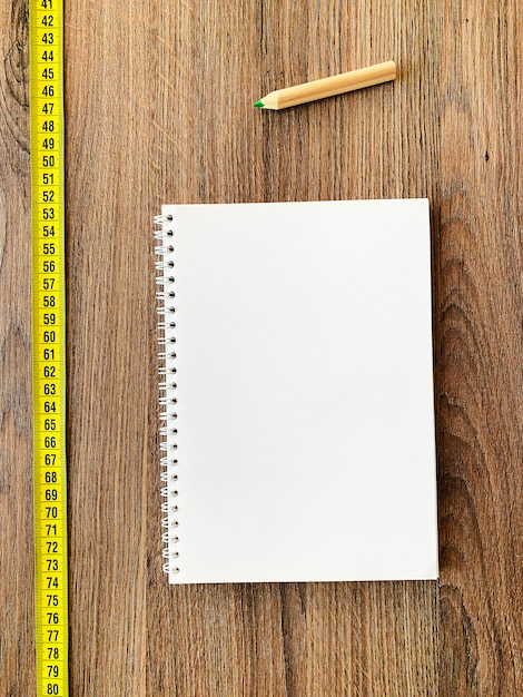 Diet . measuring tape on wooden background with book diary notepad and pen for healthy fitness background Premium Photo