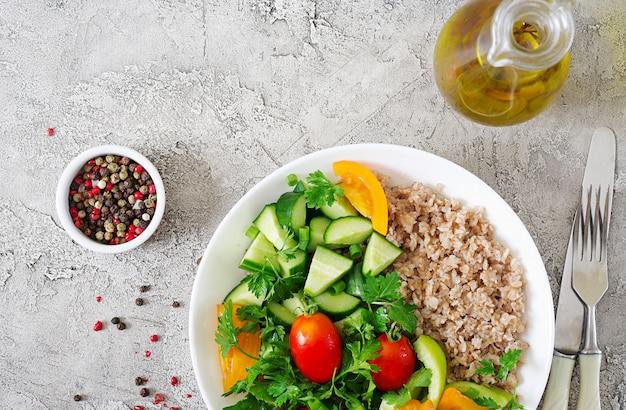 Диетическое меню. здоровый вегетарианский салат из свежих овощей - помидоры, огурцы, сладкий перец и каша на миску. веганская еда. квартира лежала. вид сверху Бесплатные Фотографии