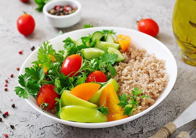 ダイエットメニュー。新鮮な野菜-トマト、キュウリ、ピーマン、お粥のボウルのヘルシーなベジタリアンサラダ。ビーガンフード。 無料写真