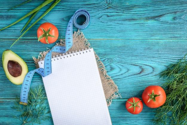 食事療法は空のノート、メニューまたは栄養プログラムを計画します。青い木製の背景に新鮮な野菜。 Premium写真