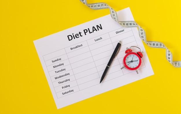Планировщик расписания диеты, рулетка, ручка и вид сверху будильника. пора начать концепцию диеты Premium Фотографии