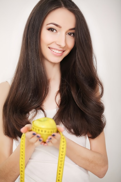 Diet, slim young woman measuring her waist with a tape measure Premium Photo