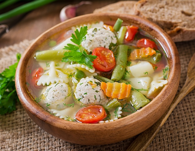 Diet vegetable soup with chicken meatballs and fresh herbs in wooden bowl Premium Photo