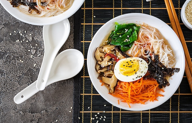 Diet vegetarian bowl of noodle soup of shiitake mushrooms, carrot and boiled eggs.  japanese food. top view. flat lay Premium Photo