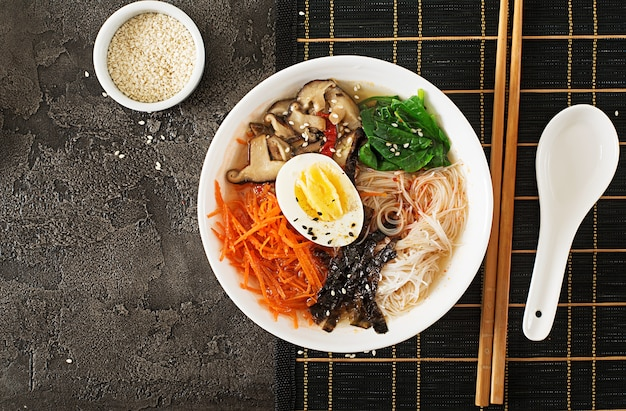 Diet vegetarian bowl of noodle soup of shiitake mushrooms, carrot and boiled eggs.  japanese food. top view. flat lay Free Photo