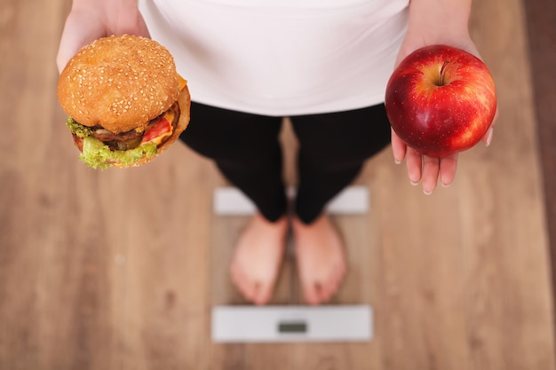 Diet, woman measuring body weight on weighing scale holding burger and apple Premium Photo