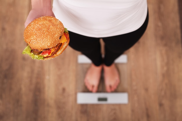 Diet. woman measuring body weight on weighing scale holding burger and apple. Premium Photo