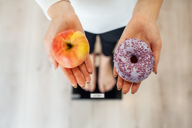 Diet. woman measuring body weight on weighing scale holding donut and apple. sweets are unhealthy junk food. dieting, healthy eating, lifestyle. weight loss. obesity. top view Premium Photo