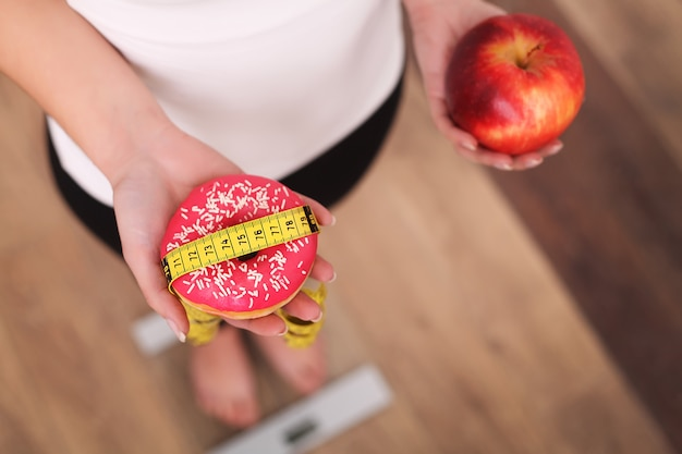 Diet, woman measuring body weight on weighing scale holding donut and apple Premium Photo