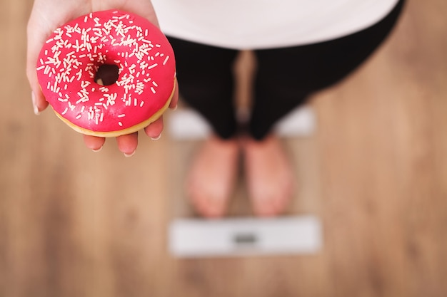 Diet. woman measuring body weight on weighing scale holding donut. Premium Photo