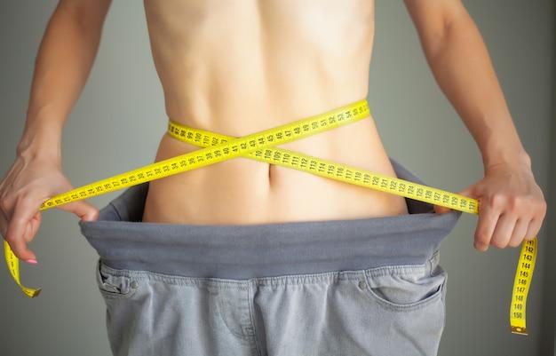 Diet. woman in sportswear measuring her waist. dieting Premium Photo