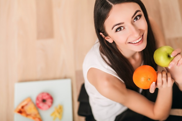 Diet. a young woman watches her figure and eating fresh fruit. the concept of healthy eating. Premium Photo