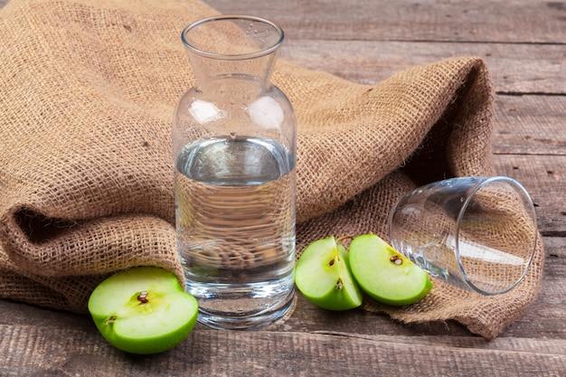きれいな水と木製のテーブルに新鮮なリンゴのリンゴのスライスと食事のデトックスドリンク Premium写真