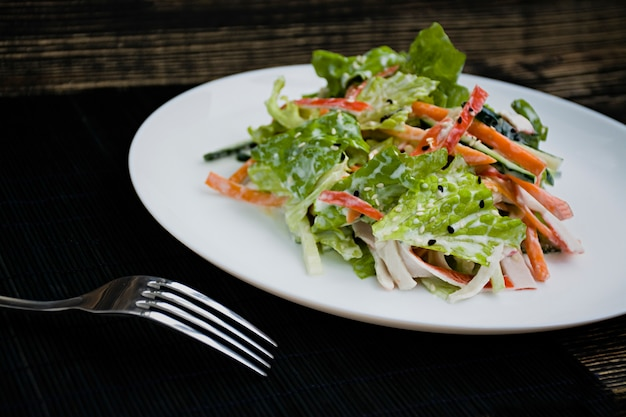 Dietary food, fresh vegetable salad with imitation of crab stick, seasoned with soy sauce and japanese sesame. cut into strips. Premium Photo