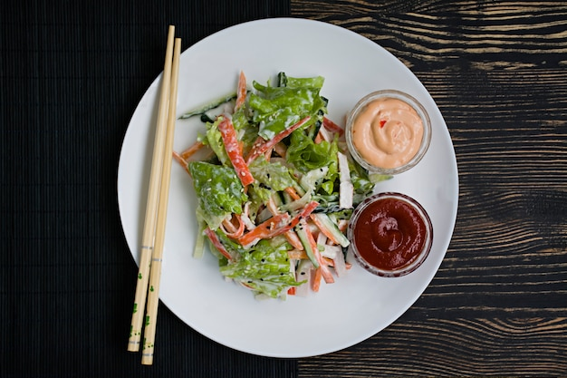 Dietary food, fresh vegetable salad with imitation of crab stick, seasoned with soy sauce and japanese sesame. Premium Photo