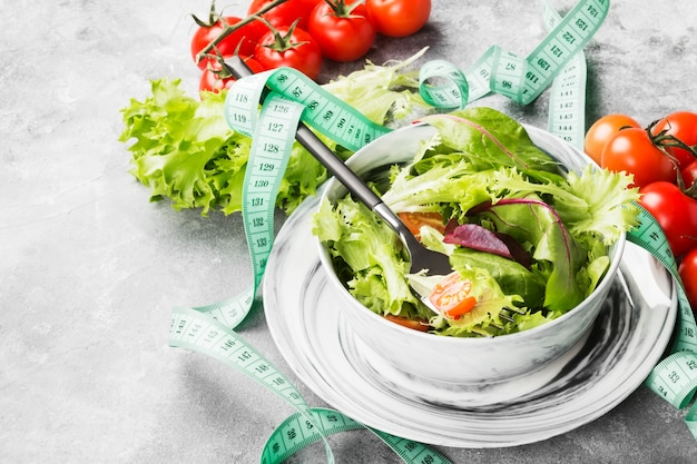 The dietary mixed greens salad and cherry tomatoes in a bowl Premium Photo