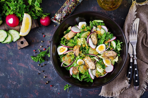 Dietary salad with mussels, quail eggs, cucumbers, radish and lettuce. healthy food. seafood salad. top view. flat lay. Free Photo