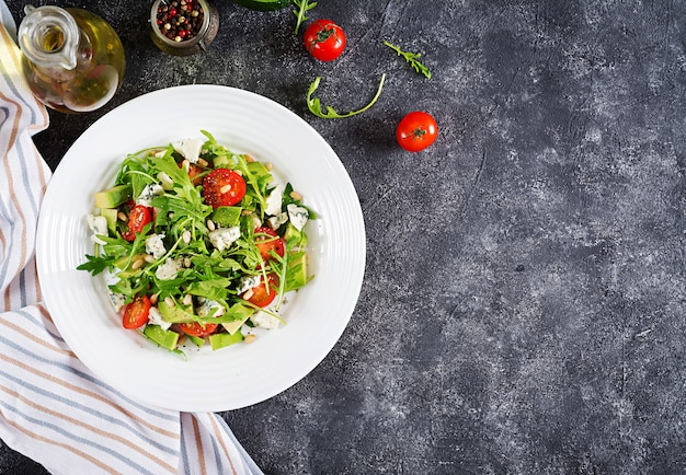 Dietary salad with tomatoes, blue cheese, avocado, arugula and pine nuts. Free Photo