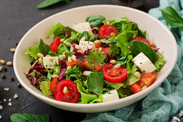 Dietary salad with tomatoes, feta, lettuce, spinach and pine nuts. Premium Photo